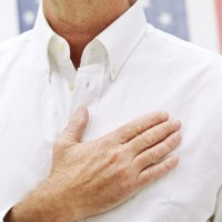 Elderly Man Standing with a Hand on His Heart in Front of the American Flag
