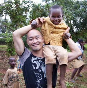 Heward Jue with child in Rwanda, photographed by Wayne Kittelson.
