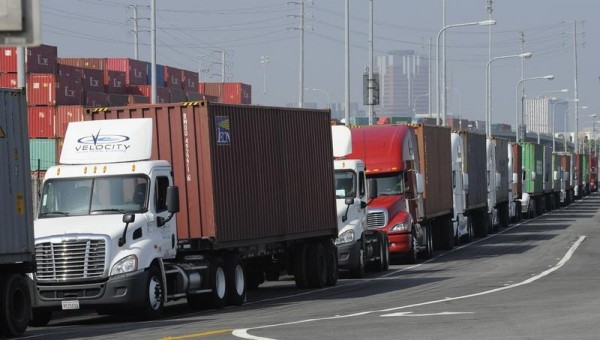 Transport trucks line up to drop off their shipping containers at the Port of Long Beach as a back-log of over 30 container ships sit anchored outside the Port in Long Beach, California, February 18, 2015. U.S. Labor Secretary Tom Perez planned to hold a second round of talks with shipping company executives and union leaders for 20,000 dock workers on Wednesday, seeking to broker a deal to end months of labor turmoil clogging cargo traffic at 29 West Coast ports. REUTERS/Bob Riha, Jr. (UNITED STATES - Tags: TRANSPORT BUSINESS EMPLOYMENT) - RTR4Q5X4
